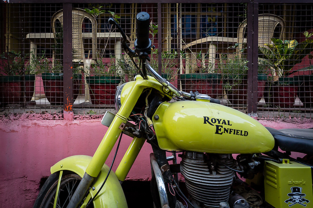 A green Royal Enfield stands against a pink wall. The Royal Enfield is one of the most famous motorbikes in India.