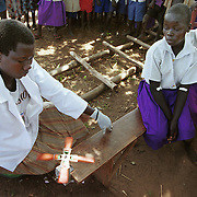 Omugo, Uganda           April, 2000<br /> <br /> <br /> School children watch closely as a lab technician uses a hand-turned centrifuge to separate blood for a second test for sleeping sickness. The technician is member of a mobile screening unit run by Medicins San Frontieres (MSF) in Omugo, Uganda. The children who test positive for the disease must have a second test to confirm the initial results. If the patient tests positive in the second test, then the mobile unit will transport them to the sleeping sickness clinic where they will be treated. The sleeping sickness clinic and screening program in Omugo is one of many run by Medicins San Frontieres throughout equatorial Africa.<br /> Photo by Lori Waselchuk<br /> <br /> horizontal/color
