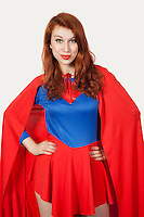 Portrait of young woman in superhero costume with hands on hips against gray background