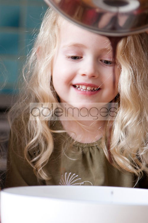 Close up of a young girl looking into a bowl