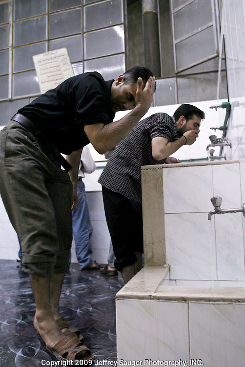 Emad Al-kasid performs Alwtho, which is washing oneself to purify the body and soul, before prayer at the Howza of Ayotollah Shirazi the Iraqi area of Damascus, Syria, Wednesday, July 16, 2003. A Howza is like a seminary where men come to study. In this Shiite Howza, the philosophy of Ayotollah Shirazi is taught. As with all Shiite, advocacy of non-violence is the pre-eminent rule. Al-kasid has been planning has been planning the trip home to Nasiriyah, Iraq, over the last year. He is visiting his immediate family is in Damascus, Syria, as hundreds of thousands of Iraqi Shiite settled in Syria after the Gulf War and their uprising against Saddam Hussein in 1991.