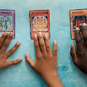 From left to right, the hands of neighbors Mariana Dilu Hernandez, 9, Stefanie Pelegrino, 7, and Davey Adria, 10, hold up Spanish language Yu-gi-oh  game cards against the wall of the main passageway of their apartment building in the Habana, Cuba neighborhood of Jesus Maria.  Yu-gi-oh cards, originally from China, are a children's game and sets of collector cards that have reached international popularity with children worldwide.  Photo by Jen Klewitz