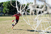 Yandri Hernandez, 15 does a trick before kicking the soccer ball into the goal while playing with his friend Cody DiNatale, 15, (not pictured) at Foss Park in Somerville, August 7, 2015.