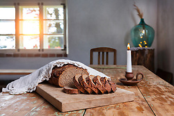 Homemade bread on rustic wooden table in Hellenurme watermill, Estonia