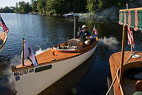 Joe Spadoni from Washington State backs out of the dock at Lees Mill , Moultonboro in his 20' Steam Launch with single cylinder engine loaded with wood fuel for the trek to 19 Mile Bay in Tuftonboro on Wednesday.  (Karen Bobotas/for the Laconia Daily Sun)