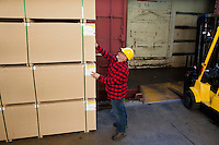 Worker inspecting wood pallet standing by fork lift truck