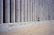 Woman reading under the watchful eye of a security camera at Lincoln Center, New York City.