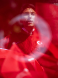 © Licensed to London News Pictures. 15/05/2018. London, UK. A supporter of Turkish President Recep Tayyip Erdogan is seen through the Turkish flag opposite Downing Street ahead of the Turkish President's arrival to Downing Street. President Erdogan will meet with British Prime Minister Theresa May later today. Photo credit: Rob Pinney/LNP