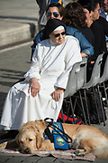 VATICAN CITY 04 OCTOBER 2017: A religious Sister sits with her service dog at General Audience with Pope Francis on October 04, 2017 at Saint Peters Square in Vatican City, Rome, Italy.
