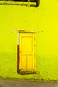 A lime green wall and yellow wooden door in Angangueo, Michoacan, Mexico. Angangueo is a tiny, remote mountain town and the entry point to the Sierra Chincua Monarch Butterfly Sanctuary.