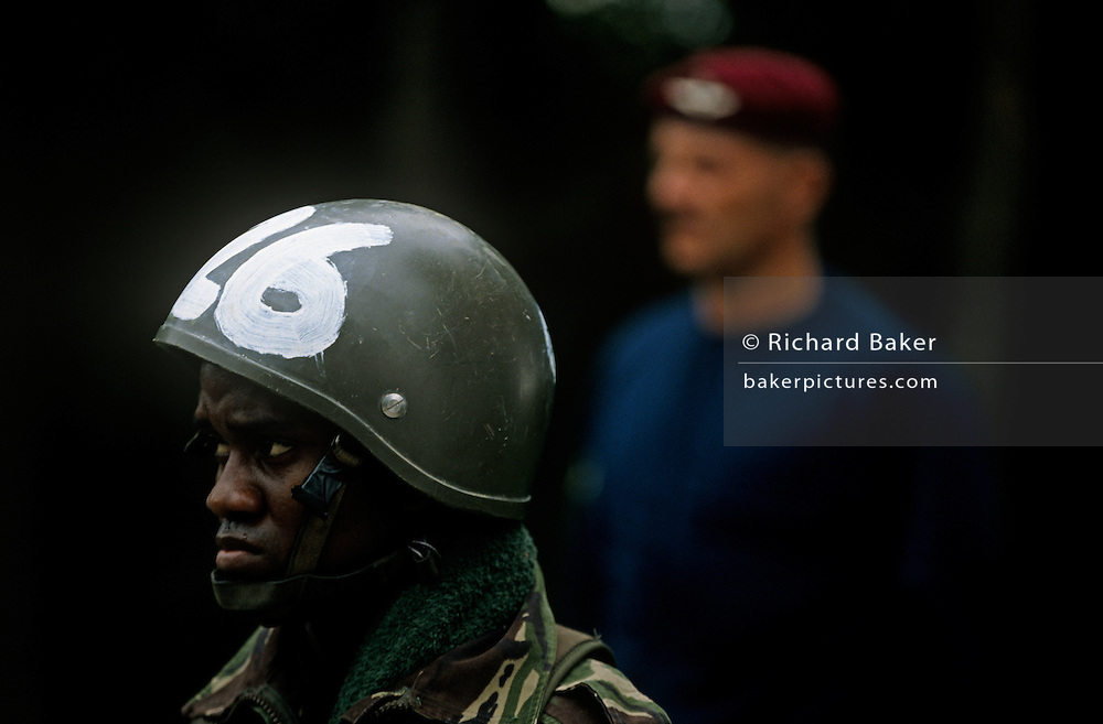 Wearing a large green helmet with the number 26 painted on the front, a worried-looking black soldier recruit gazes into the distance in front of a white army  instructor at the large Garrison at Catterick, England. Here, the Parachute Regiment (The Paras) - hold part of their famous basic training programme called Pegasus (P) Company. The most notorious selection procedure in the British Army. After initial recruitment, each student is sent to either pass or fail a set of 9 events from which a total score of 90 points is possible. 58% or more passes, less fails. Events like the 18 mile Forced March followed by a further 5 miles can earn 10 points though this will inevitably prove too much for many young man, desperate to pass P Company and earn his prestigious beret (Like the Foreign Legion).