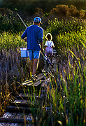 Grandfather and granddaughter walking along a marsh path to go fishing. Cape Cod