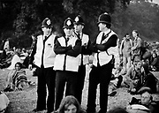 Four white male policemen stand grouped together, Glastonbury 1997