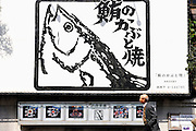 A man walks past a menu and giant poster of a restaurant claiming to be Japan's first to specialize in grilled tuna head at  Misaki Port, west of Tokyo, Japan .