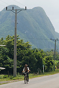 A man rides his bicycle along a road overlooked by a large mountain formation called mogote near Vinales, Cuba.