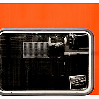 The close-up of a train window in which a waiting travelers reflected.