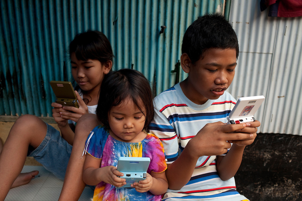 Kids play electronic games on the street in Tambor, Jakarta, Indonesia.