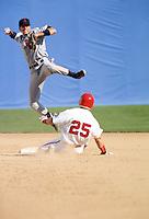 Baseball player sliding into base while man throws ball