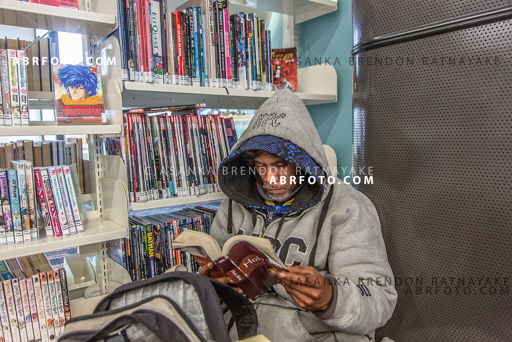 Joseph Takairangi sits in the corner of the New Lynn War Memorial Library reading the Bible on the 6th of June 2018. The homeless often use the Library during the day taking advantage of the free internet and to keep out of the cold during winter. Asanka Brendon Ratnayake for The New York Times.