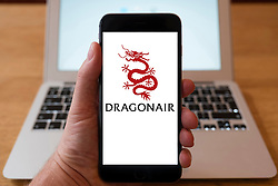 Using iPhone smartphone to display logo of Dragonair airline from Hong Kong