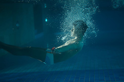 Swimmer in a pool with bubbles around him from jumping in the water taken from underwater