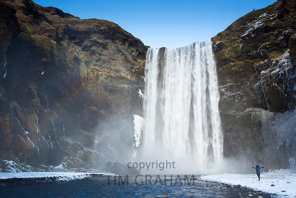 Tourist at spectacular Skogar waterfall - Skogarfoss - in South Iceland with gushing glacial melting waters