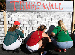 Oct 19, 2016 - Las Vegas, Nevada, U.S. - Anti-Trump protesters write on a 'Trump Wall' in front of Trump International Hotel Wednesday as protesters built a wall of Taco Trucks outside the hotel. The third and final debate is being held Wednesday at Las Vegas Nevada University. (Credit Image: © Gene Blevins via ZUMA Wire)