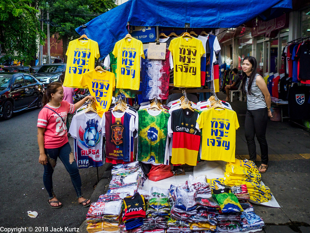 "03 JULY 2018 - BANGKOK, THAILAND: Venders in Bobae Market, a clothing market in Bangkok, sell World Cup tee shirts and yellow tee shirts that say ""Long Live the King"" in advance of the Thai King's birthday. The birthday of King Maha Vajiralongkorn Bodindradebayavarangkun, Rama X, is 28 July. The King, the only son of Thailand's late King Bhumibol Adulyadej, became the King of Thailand in 2016 after the death of his father. King Vajiralongkorn was born on 28 July 1952, a Monday. In Thai culture each day of the week has a color, and yellow is the color is associated with Monday, so people wear yellow for the month before his birthday to honor His Majesty.   PHOTO BY JACK KURTZ"