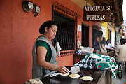 A woman makes pupusas, a local snack, outside a restaurant in the town of Valle de Angeles, Honduras on Friday April 26, 2013.