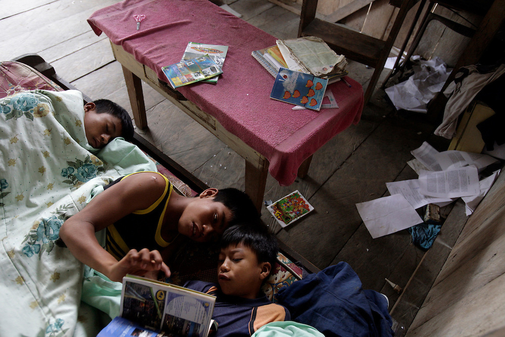 The Grefa kids at their home in San Pedro Sumino. The middle kid is a cousin who has moved in with the Grefas. He enjoys reading to his younger cousin during a rainy evening.