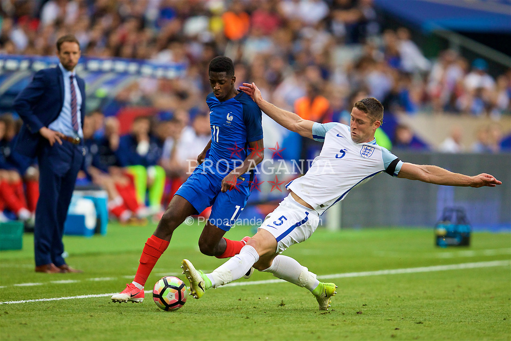 PARIS, FRANCE - Tuesday, June 13, 2017: England's Gary Cahill tackles France's Ousmane Dembélé during an international friendly match at the Stade de France. (Pic by David Rawcliffe/Propaganda)