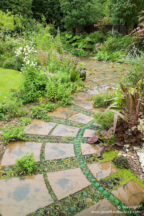Patio with plants planted amongst paving slabs and decorative use of sunken upturned bottles and gravel. Version after rain.