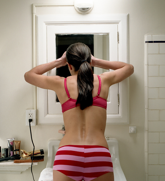 young woman 20's something, checking face in bathroom mirror, rear view