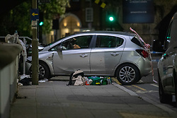 © Licensed to London News Pictures. 13/05/2020. London, UK. A car that has collided with a wall on Lombard Street sits on the pavement alongside medical packs and blooded items of clothing, the car has blood on the back door. Police were called at around 1800BST on Wednesday, 13 May, to reports of a man with a knife in Lombard Road, SW11. There were also reports of a car in collision with a wall in Lombard Road. Officers attended the location and found two men injured - one had cuts to his arms and the other cuts to his legs. Officers believed the two men had been travelling in the car. Both have been taken to hospital, where their injuries are not believed to be life-threatening. Investigations at the scene led officers to Vicarage Crescent, SW11, where they found two other injured men. Both were taken to hospital with non life-threatening injuries. Photo credit: Peter Manning/LNP