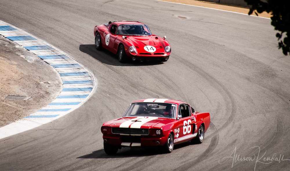 1966 Shelby GT 350 driven by Mark Cane leads a 1968 Bizzarrini Strada GT driven by John Fudge through the corkscrew at Laguna Seca during the Rolex Monterey Motorsports Reunion 2013