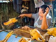 19 NOVEMBER 2014 - BANGKOK, THAILAND: A vendor burns the feathers off of a chicken in Khlong Toei Market in Bangkok. Between July and September the economy expanded 0.6 percent compared to the previous year, the National Economic and Social Development Board (NESDB) reported. Thailand's economy achieved a weak 0.2 per cent growth across the first nine months of the year. The NESDB said the Thai economy is expected to grow by 1 percent in 2014. Authorities say the sluggish growth is because tourists have not returned to Thailand in the wake of the coup in May, 2014, and that reduced demand for computer components, specifically hard drives, was also hurting the economy. Thailand is the leading manufacturer of computer hard drives in the world. The Thai government has announced a stimulus package worth $11 billion (US) to provide cash handouts to farmers and promised to speed up budget spending to boost consumption.   PHOTO BY JACK KURTZ