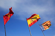 Flags of Jativa or Xativa, Spain, and Valencia flying against blue sky, Jativa castle, Spain