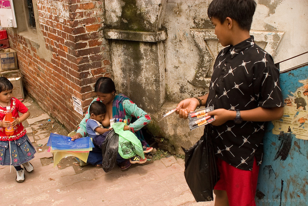 A mother breast feeds an older child while selling goods on the streets of Kathmandu, Nepal.www.crystalstreet.net