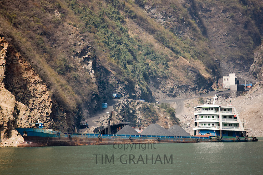 Freight ship being loaded with coal from delivery trucks on the shore, in Three Gorges area, Yangtze River, China