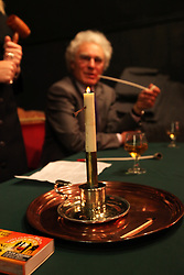 © under license to London News Pictures.  13/12/2010..Church warden Dr Chris Newman watches on at the age-old tradition of a candle auction. The auction, held every three years, is where people bid to lease a local meadow while a candle containing a horse-nail burns...The person with the bid when the nail drops out of the specially-made tallow candle is declared the winner...The event, which originates from the early 1800s, was held at Aldermaston Parish Hall, Berkshire, with the local vicar as the auctioneer. Church wardens, in-keeping with tradition, are given pipes, although they were not allowed to light them...Picture credit should read: Rebecca Mckevitt/London News Pictures