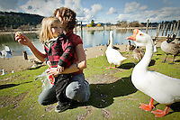 JEROME A. POLLOS/Press..Ezekiel Heward, 2, keeps a watchful eye on an approaching goose as his mother, Brandi Elder, feeds the birds Monday gathering along the Spokane River near North Idaho College.
