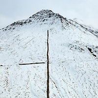 Wooden marker by the road near  the summit of the Furka Pass (2431m) connecting Uri and Valais in the Swiss alps. Such markers are used to show the position of the route when covered by snow. Photographed shortly before the road closed for a seven month winter. Historically this area, around Uri belonged to the National Redoubt, the final Swiss line of defence in the high alps, and is checked with the remains of millitray installations, many of them underground, still camouflaged.