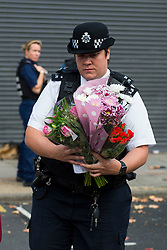 © Licensed to London News Pictures. 11/10/2015. London, UK. A police officer carrying flower left at the scene outside the RE bar in Field End Road, Eastcote, Hillingdon where a man was stabbed to death early this morning (SUN). The victim is believed to be  21-year-old Josh Hanson from Kingsbury.  Photo credit: Ben Cawthra/LNP