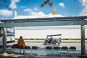 A monk waits at a bus stop outside the Grand Palace in Bangkok, Thailand as a tuk-tuk rolls by. Bangkok, Thailand, November 2015. Photograph © 2015 Darren Carroll.