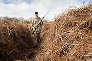 Carrying a Lee Enfield rifle and bayonet, Rifleman Stuart Gray walks through a overgrown trench in a practice battlefield, where thousands of troops trained before embarking for the battlefields of Europe during World War One. The trench system was been discovered by chance on the Browndown Ministry of Defence site in Gosport, Hampshire, England. March 6, 2014. AFP PHOTO / CHRIS ISON.