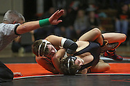 Prairie's Josh Wenger (from left) scores near fall points on Linn-Mar's Manny Jeffery during the 138-pound bout of the dual between Linn-Mar and Cedar Rapids Prairie at Prairie High School in Cedar Rapids on December 12, 2013.