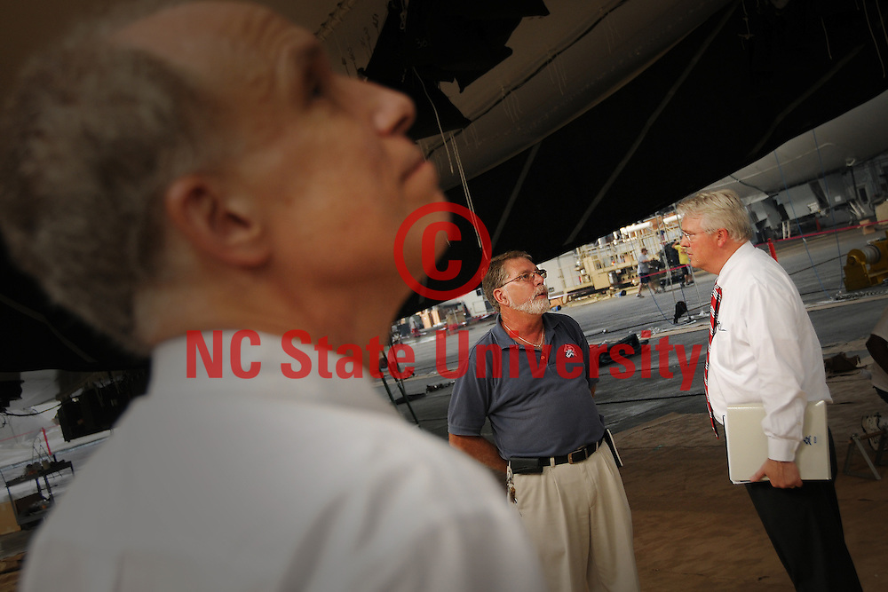 Chancellor Randy Woodson (right) listens to TCOM's Steve Chalk as Tom White looks up at an aerostat under construction above his head in the massive hangar.