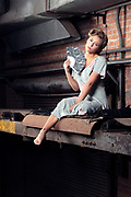 Brenna Smith by Gerard Harrison in vintage 1940s dress posing on an elevated conveyor belt in the abandoned Imperial Sugar mill, Sugar Land, Texas.