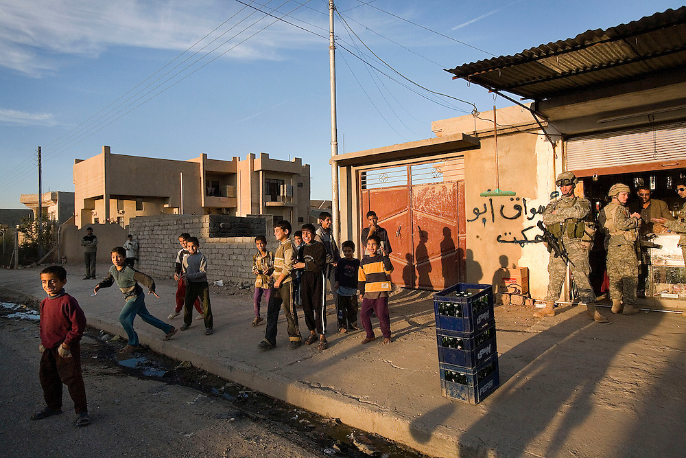 Children play on the streets while members of the 1st Infantry, 17th Regiment, help Iraqi forces patrol in western Mosul, Iraq, Dec. 11, 2005. This is part of an effort to provide security in preparation for Iraq's first post-Saddam parliamentary elections. The western sector is home to Mosul's primarily Sunni population, which has been resistant to the American presence in Iraq.