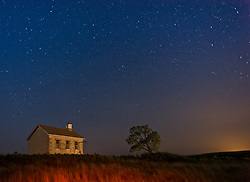 The evening sky reveals stars over the Lower Fox Creek Schoolhouse located in the Tallgrass Prairie National Preserve in the Kansas Flint Hills. The school, on the National Historic Register of Historic Places, was built on land donated by cattleman Stephen F. Jones. Built in 1882, the one-room school had its first classes in 1884. Typical enrollment was between one to 19 students of all grades. The school was closed in 1930 and restored in 1968 by the Garden Clubs in the Mid-East District of Kansas. The glowing light on the right is from the city of Emporia some 20 miles away to the east. The 10,894-acre Tallgrass Prairie National Preserve is located in Chase County near the towns of Strong City and Cottonwood Falls. Less than four percent of the original 140 million acres of tallgrass prairie remains in North America. Most of the remaining tallgrass prairie is in the Flint Hills in Kansas. Tallgrass Prairie National Preserve is the only unit of the National Park Service dedicated to the preservation of the tallgrass prairie ecosystem. The Tallgrass Prairie National Preserve is co-managed with The Nature Conservancy.